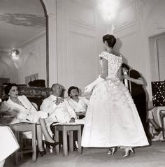 Christian Dior works with Mitzah Bricard (left) and Marguerite Carré (right) on the Première Soirée dress for the autumn/winter 1955 haute couture collection.