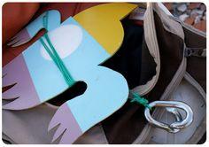 """Pequenos pássaros de madeira coloridos aparecem, eventualmente, """"voando"""" pela fiação de postes da cidade. Nomeados de Lovebirds, os pássaros são obra do artista visual carioca, Rodrigo Villas, que intervém na paisagem urbana como forma de """"protesto poético""""."""