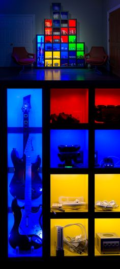"""Game Room """"Tetris Wall"""" stores all of the controllers, games, discs and cartridges. Great lights and colored storage shelves."""