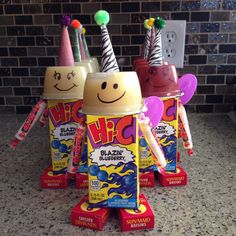 Juice box, applesauce, smarties and raisins all hot glued together. Spoon taped on the back. Smiley face with sharpie and party hats with pom poms. Easy birthday treat for school.