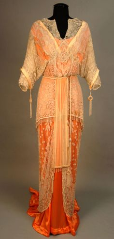 Tangerine silk satin gown from the 1910s. Weighted fishtail hem. Two-layer overdress with crystal and mother of pearl beads. The sleeves of the overdress have beaded tassels and ring drops. Matching drops are at the end of a chiffon panel set in the cutaway skirt front, with a shorter, fringed layer of  net.