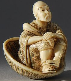 Ivory netsuke depicting a man seated in a large basket
