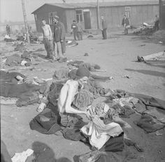 THE LIBERATION OF BERGEN-BELSEN CONCENTRATION CAMP, APRIL 1945  ~  A camp inmate, reduced by starvation to a living skeleton, delouses his clothes.
