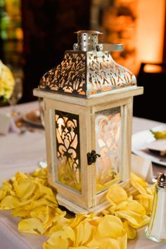 Lanterns with flower petals around it for a  simple but elegant table decor