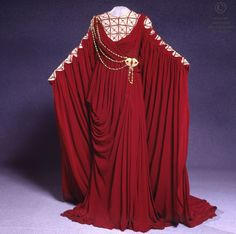 Opera National de Paris Robe draped crepe burgundy. Neckline and long sleeves embroidered tulle with golden flesh, red stones and gold braid beads. Starting from a gold chain shoulder to waist attached by a fibula. Brown synthetic wig.