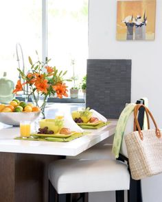 Dining Room: Breakfast With White Dining Table. white dining table. white upholstered dining chair. green place mat. silvery fruit bowl. glass vase. orange flowers. flower painting.