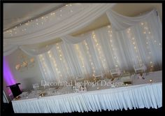 Bridal backdrop with extending swagging and fairy lights for hire