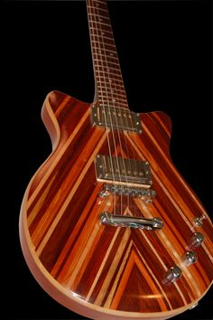 B51 Chevron electric guitar, lovely striped wood in warm browns, orange tones. RESEARCH #DdO:) - INSTRUMENTS FOR JOY - https://www.pinterest.com/DianaDeeOsborne/instruments-for-joy/ - Slight double cutaways give guitarist player easy access to high frets for fingering & slide work. Crosbie Scrapback V top gives B51 unique presence on stage. Sonic acoustics capabilities hardware: Seymour Duncan Seth Lover double Humbuckers allow for a range of tone & sound. $2,800 August 2015.