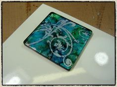Tim Holtz alcohol ink  and stamp technique that can be used on any smooth surface.