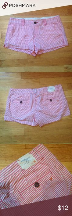American Eagle Striped Shorts American Eagle Shorts.  Pink and white striped.  Brown buttons on the front and back. Orange logo.  Zipper closure. Belt loops. 100% Cotton. American Eagle Outfitters Shorts Cargos