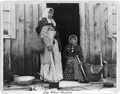 1894 photo entitled: The Clam Diggers. Two elderly Indian women at doorway of building, with small pile or cluster of clams and poles and sacks, used to gather clams? Modoc Native American