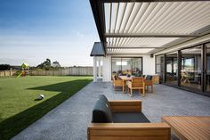 Brodie & Niki Retallick's outdoor entertainment patio with concrete flooring, louvre shutters and wooden furniture #outdoorliving #outdoorfurniture #sunlouvre #outdoorentertaining  #house #brodieretallick #generationhomes