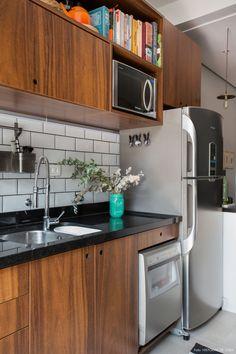 Cozinha tem armários de madeira, subway tiles com rejunte escuro.