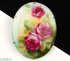 Description: Vintage oval hand painted floral motif porcelain brooch; decorated with ruby red roses and greenery; brass setting. Designer/Makers Marks, Hallmarks, Tags: Unsigned. Age: Circa 1920's-194