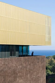The glazed public areas of this cultural centre on the French island of Corsica are sandwiched between a solid concrete base and an upper storey clad in perforated golden metal