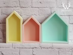 Three house-shaped shelves for trendy kid's room decor.
