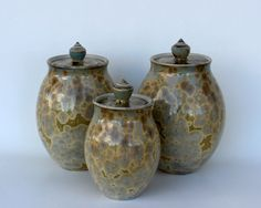 This canister set was thrown on the wheel from a fine porcelain clay. It was trimmed, bisque fired, and then glazed with a handmade amber crystalline glaze. The inside of each piece was carefully glazed with a silky white liner glaze. The pieces stand 7.5, 9, and 9.5 inches tall, respectively. Measurements include the finial (circular knob on the lid). Crystalline glazing is a unique glazing technique in which crystals are grown on the surface of the pot during the firing process. Good…