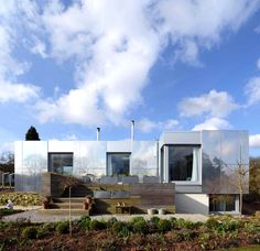 house with a mirrored exterior / house called Green Orchard. Located in England, outside of London.  Carbon neutral smart home was created by Paul Archer Design.  While the exterior looks like it is mirrored it is actually made up of special aluminum coated panels that help the house use less energy &  *** makes the house actually blend ***** with the surroundings *** by reflecting ***** the world around it!