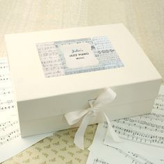 A beautiful keepsake box for storing sheet music, notes and books, personalised with your own text. This large personalised keepsake box is perfect for keeping all of your sheet music in one place, and can also be used for storing music books, notes and other bits and bobs. The box is covered with a matte cream paper and printed on the inside with a polka dot pattern. It has a magnetic closure and is finished with a high quality cream ribbon for an extra special touch. Each box has three ...