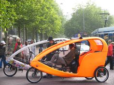 Bike taxi in Amsterdam. Bike taxis are a new kind of urban gondola and the perfect way to get around Amsterdam. No air pollution. No noise, apart from the odd squeak and the occasional bell ring. No hassle. Bike taxis are three-wheeled post-modern style rickshaws with open windows and fluorescent sides. They are pedal-powered and come with two small batteries to enable the driver to steer over Amsterdam's infamous bridges or to carry extra heavy passengers.