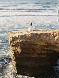 """For this California wedding, newlyweds were photographed on dramatic coastal bluffs. """"The rocky path down the cliff in this photo was not th..."""