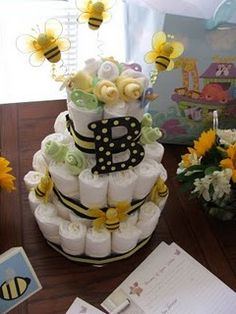 "Bee-themed diaper cake and baby shower invitations for a ""What will it Bee?"" baby shower."