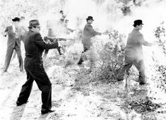A group of men in suits and hats are obscured by the smoke from the guns, including Thompson submachine guns, shotguns, and revolvers, that they are firing in a shrubland, USA, 1930s. (Photo by Vintage Images/Getty Images)