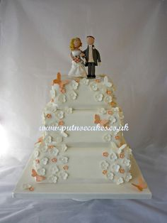 Ivory wedding cake with hints of coral, handmade bride and groom topper.