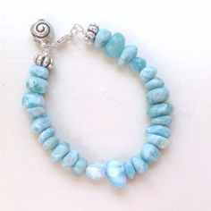 This larimar bracelet is made of blue larimar chip gemstones, sterling silver: beads, spacers, shell charm, lobster