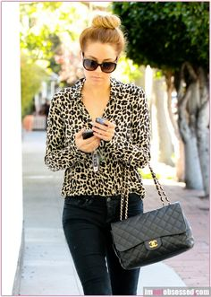 A classical look with animal print top, black jeans, and a Channel handbag.