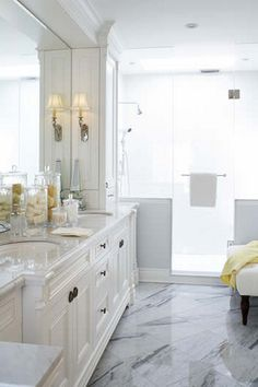 Off-white bathroom with marbled floors and glass shower