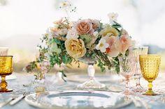mesa posta em tons pastel e dourado com flores combinando.
