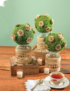 Trim up your tea table with a trio of topiaries. Start by embellishing moss-covered foam spheres with pretty paper rosettes (Scrapbooking Department). Then display them atop inverted petite hurricane vases covered in burlap ribbon and trimmed with cotton webbing.