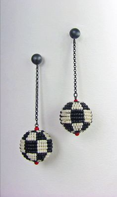 Black and White Mod Earrings by Julie Long Gallegos. Tiny size 15/o seed beads are needlewoven around perfect round inner forms to create this bold but delicate classic chain-drop checkerboard ball. Brilliant 2mm coral beads accent the join to oxidized sterling silver chain and post. Lightweight and wearable at a total length of 2.3 (60mm) and width of 11/16 (18mm)..