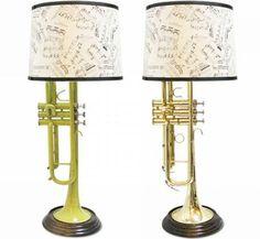 Lámparas hechas con instrumentos musicales. En las pantallas, partituras musicales.