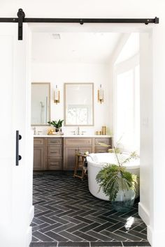 Neutral bathroom with soaking tub and offset by black herringbone pattern tile floor. #decorating #details #inspiration #design #bathroom #bathroomideas #bath #soakingtub #calm #neutral #decorating #herringbonepattern
