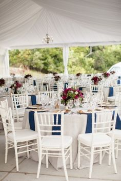 Round white reception tables with blue napkins | floral design by http://www.hollychappleflowers.com/ | photography by http://www.timmesterphoto.com/