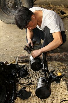 A mechanic works on pistons for a diesel engine on a collective farm in Dongbong. north korea