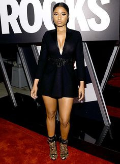 Nicki Minaj looks sleek in a black trapeze blazer dress by Saint Laurent with gold spiked booties from Giuseppe Zanotti.