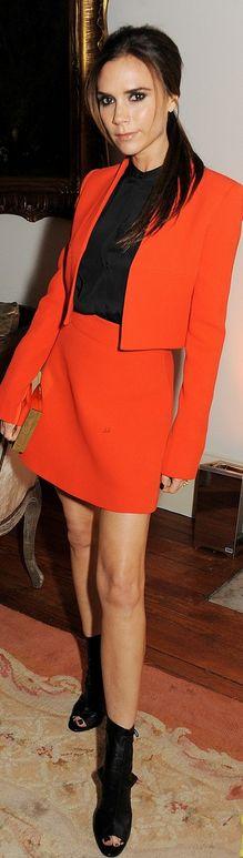 Who made  Victoria Beckham's black shoes, clutch handbag, black button top, orange skirt, and orange jacket that she wore in London on November 28, 2012?