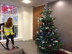Clearing away a few stray needles after we've finished decorating this Christmas tree in a Reading office.