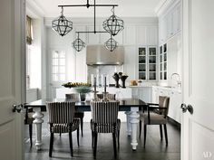 The kitchen and breakfast area of a London home by decorator Hubert Zandberg and architectural designer Jan Swanepoel features white cabinets and Cox London light fixtures.