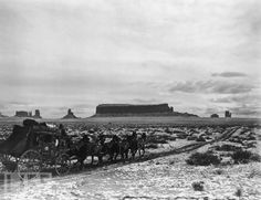 A stagecoach pulled by six horses travels along a dirt road through a valley dusted by snow in Monument Valley, Arizona, in 1905.