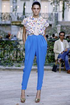 Nos enamora el pantalon con volumen de talle alto azul cielo combinado con un top blanco. El toque Premium lo da la torera de manga corta, en la que predomina el color blanco con detalles azules, dorados y rosa fucsia.