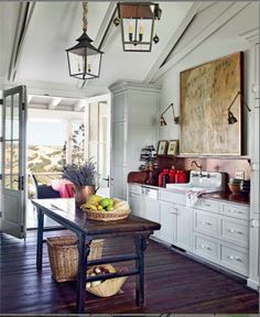 Rustic Kitchen - no upper cabinets, brass wall sconces lights and art over sink, side floor to ceiling cabinets, copper backsplash farmhouse table island with lantern pendants, wood plank floors, opens to covered porch/outdoor dining space