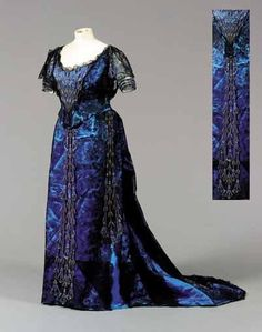 Ball gown, Worth, ca. 1900. Kingfisher blue satin overlaid with black Chantilly lace. Bodice and skirt embroidered with sequins and pearlized beads with papyrus blooms.