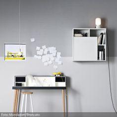 Der Schreibtisch im minimalistischen Arbeitsbereich ist platzsparend und funktional. Als Sitzgelegenheit dient ein Hocker, im quadratischen Regal an der Wand finden Bücher und Arbeitsutensilien Platz.