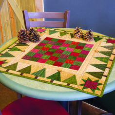 The simple design of Holiday Games, by Jen Daly, is perfect for a favorite collection of scraps. And, who doesn't love scrap quilt patterns? Don't be afraid to mix quilting cottons and flannels. You can even add quilting embellishments, like additional buttons or beads, for a special holiday touch to this table topper.
