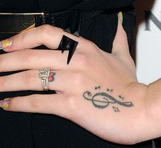 Cher Lloyd showing off her hand tattoos and rings