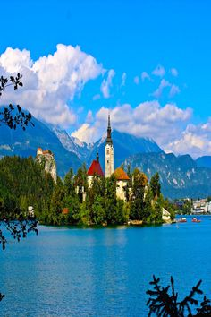 Views in Lake Bled, Slovenia: Church of the Assumption in the middle of the lake, the medieval castle on the hill and the Alps in the background.
